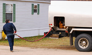 oil delivery man with hose from heating oil tanker